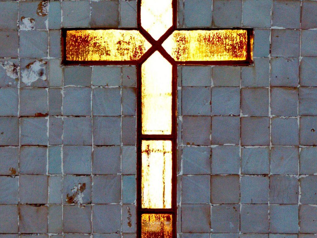 The cross by the Farol Ponta do Arnel awakened by the sun.