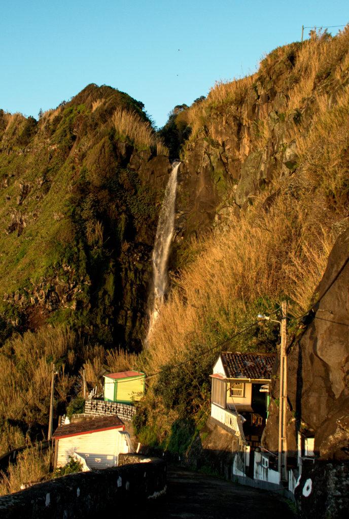 Waterfall by Farol Ponta do Arnell illuminated by the rising sun.