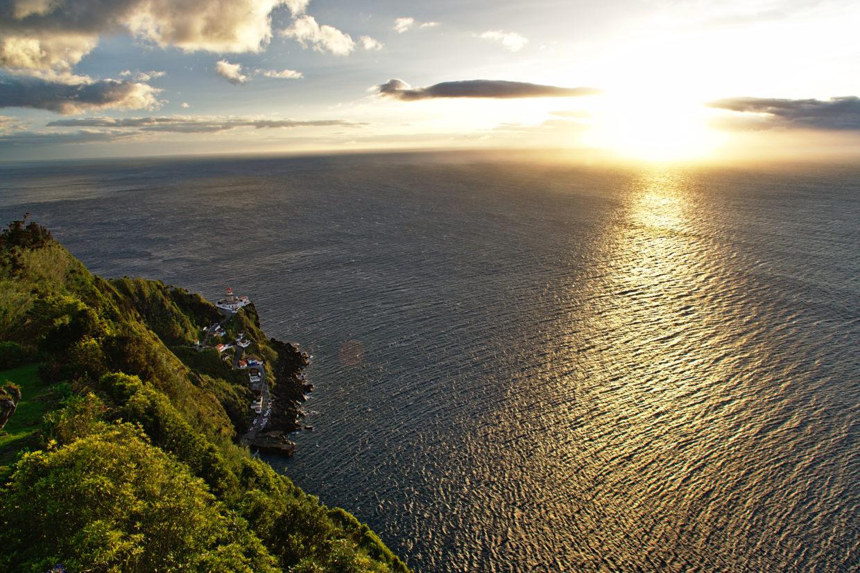 The rising sun paints the Farol Ponto do Arnel and the Atlantic ocean orange.