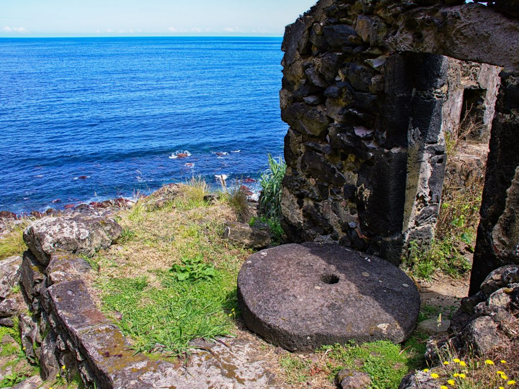 Ruin of the watermill by the Praia da Viola with an old millstone in front of the blue Atlantic.