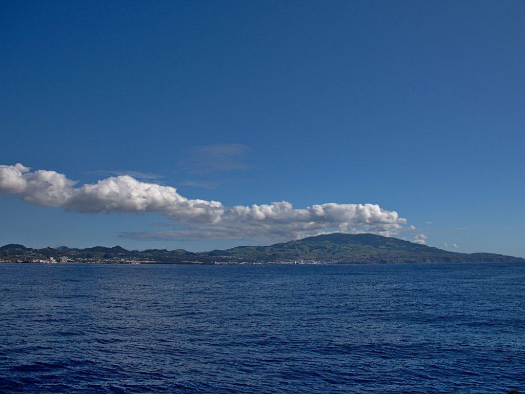 São Miguel bei Ponta Delgada von See aus mit Wolken an den zentralen Bergen